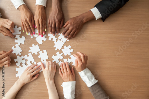 Hands of multi-ethnic team assembling jigsaw puzzle, multiracial group of black Canvas