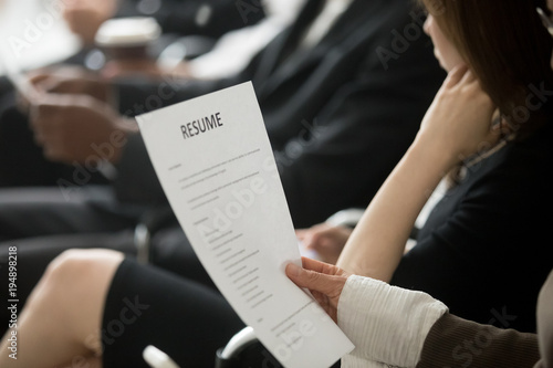 multiracial business people waiting in queue sitting in row holding