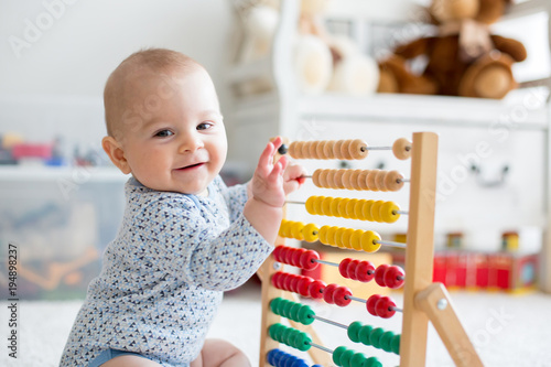 Fototapeta Cute little baby boy, playing with abacus at home