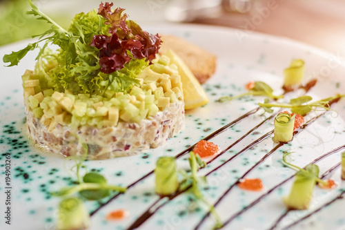 Deurstickers Klaar gerecht Beautifully served dish. Appetizing salad with herring, avocado and toasts served with lettuce and lemon. Delicious dinner on plate.