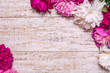 Border of peonies on a wooden background with empty space for text. Floral design. Pink and purple spring flowers.