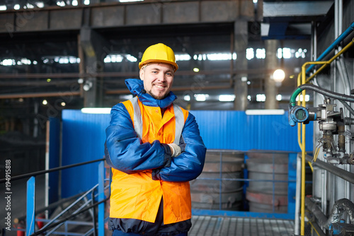 Fotografía  Portrait shot of handsome bearded machine operator wearing reflective vest and hardhat standing at spacious production department of modern plant with arms crossed and looking at camera