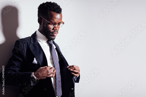 Fotografía  african business man with glasses in jacket and tie looks away