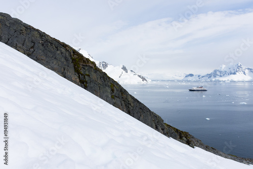 Ship seen in Paradise Bay viewed from the Antarctic Peninsula. Snow and a ridge of rocks are seen in the foreground.