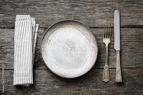 Table setting with vintage silverware, empty plate and napkin. Top view with copy space for text