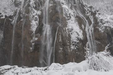Fototapeta na wymiar Big waterfall at Plitvice Lakes National Park. Winter scenery.