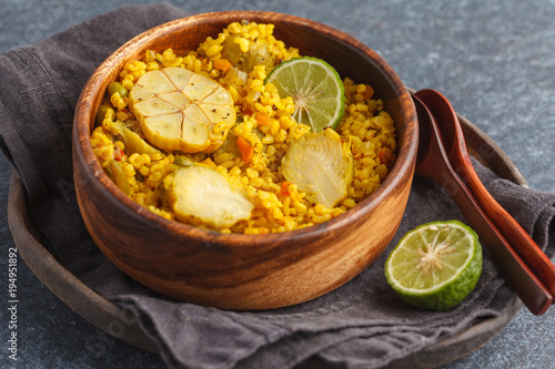 Curry bulgur with vegetables in wooden bowl. Dark background, vegan meal concept.