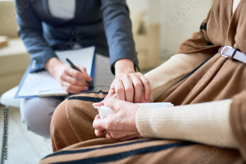 Fotografía  Close up of female psychologist holding hand of senior woman during therapy sess