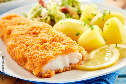 Fototapeta Crispy breaded fish with potatoes in close up obraz