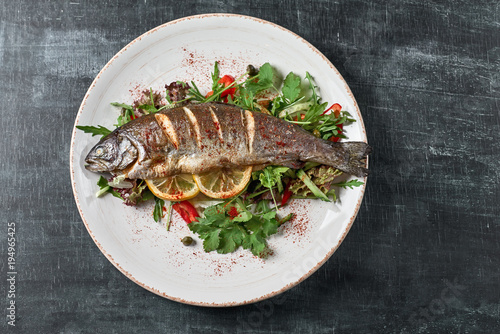 Fotografia Hot fresh delicious roasted whole trout barbecue with fresh herbs and lemon, on