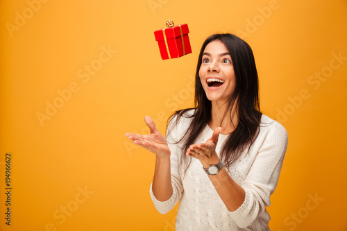 Photo Portrait of a cheerful young woman catching small gift box