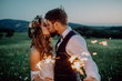 canvas print picture - Beautiful bride and groom with sparklers on a meadow.