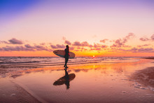 Silhouette And Reflection Of Surfer Girl With Surfboard On A Beach At Sunset. Surfer And Ocean