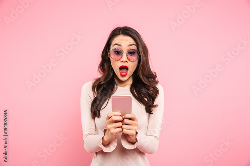 Fotografía  Surprised woman with red lips typing text message or scrolling social network us