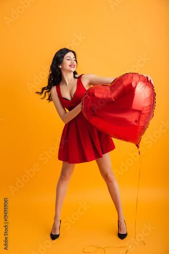 921eea503e7 Full length photo of happy young woman in red dress having fun with big  heart air balloon in hand