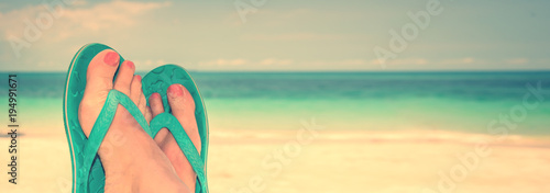 Woman feet with blue flip flops, beach and sea in the background, panoramic travel concept