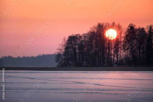 Scenic sunset with big sun at winter evening in Finland