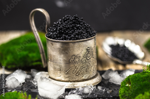 black caviar in a silver bowl with ice and a silver spoon on darck background. silver black caviar .