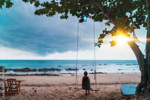 Woman sitting on swings on beach