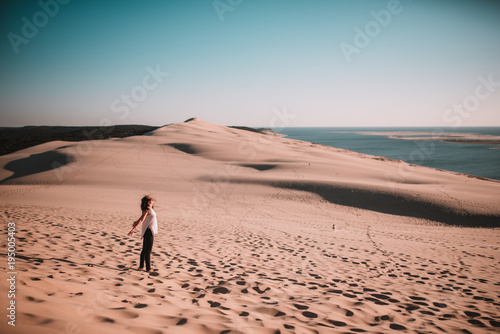 Woman standing on sand and enjoying sun