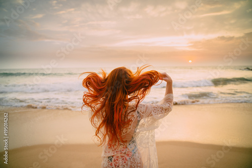 Canvas Print young red-haired woman with flying hair on the ocean coast at sunset, rear view