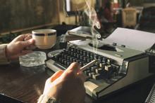 Handsome Writer Typing On Old Typewriter. Smoking Cigar And Drinking Coffee.