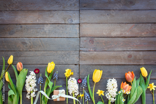 Spring flowers with a gift on vintage planks