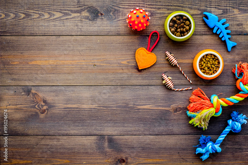 Pet care concept. Toys near bowls with animal feed on dark wooden background top view copy space