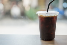 Close Up Of Take Away Plastic Cup Of Iced Black Coffee (Americano) On Wooden Table.