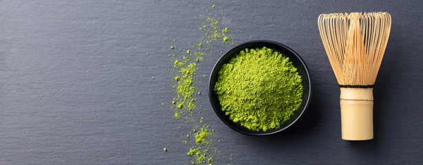 Matcha green tea cooking process in a bowl with bamboo whisk. Black slate background. Copy space. Top view.