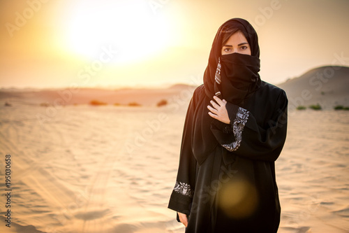 Portrait of beautiful Arab woman in the desert during sunset.