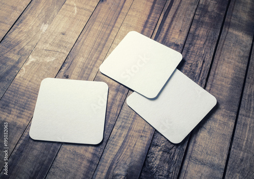 Blank white square beer coasters on wood table background.