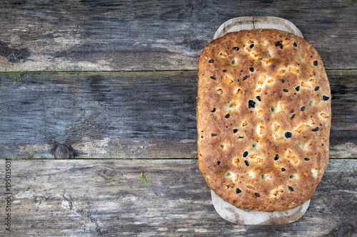 Fotografering Traditional Italian focaccia homemade bread with tomatoes and olives, on a wooden background and copy space