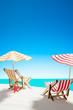Two sun loungers under an umbrella on the sandy beach by the sea and the sky with copy space