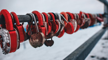 Red And Golden Locks In The Form Of Hearts Hanging On A Metal Fence At A Small Depth Of Field