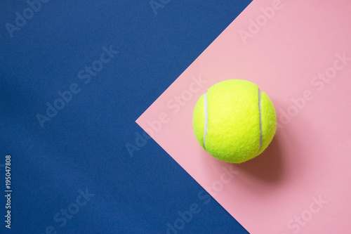 Photo Tennis ball on blue and pink paper background