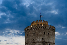 The White Tower Of Thessaloniki, Greece With Waving Greek Flag On Top