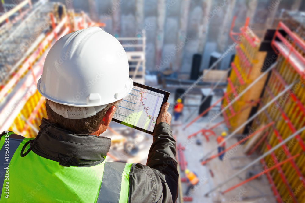 Fototapeta civil engineer or architect on construction site checking schedule with tablet computer