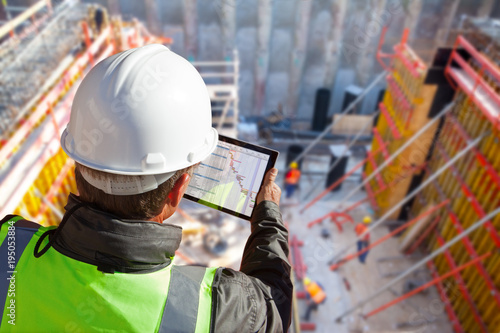 Fotografiet  civil engineer or architect on construction site checking schedule with tablet c
