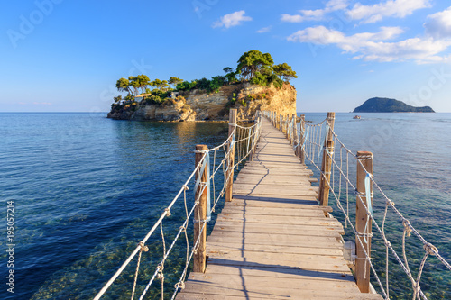 Wooden bridge from Agios Sostis leading to small rocky island. Bay of Laganas, Zakynthos island, Greece.