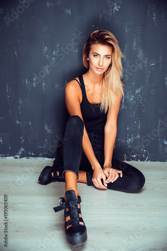 Fotografía  Young stylish blonde in black sitting with legs apart on floor looking at camera