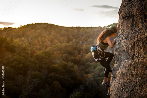 Fotografie, Obraz  Female climber on a wall climbing at sunset
