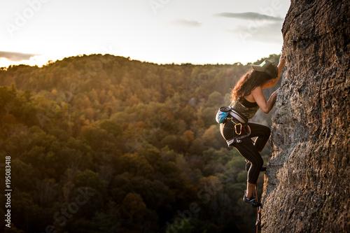 Fototapeta Female climber on a wall climbing at sunset obraz