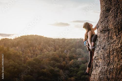 Obraz Female climber on a wall climbing at sunset - fototapety do salonu
