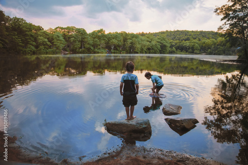 Photo children caught fish in the lake. boys playing near the water
