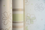 Two rolls of wallpaper stand against the wall with floral wallpaper