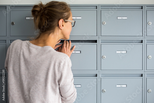 Fotomural Pretty, young woman checking her mailbox for new letters