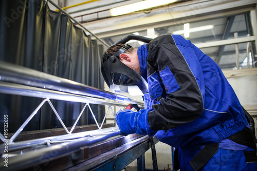 Industrial workers welding metal with many sharp sparks, Welder