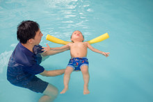 Asian Father Take Cute Little Asian 18 Months / 1 Year Old Toddler Baby Boy Child To Swimming Class In Thailand, Kid Learn To Float With Pool Noodle With Dad At Indoor Pool, Shallow Depth Of Field