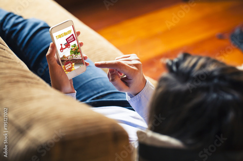 Woman ordering take away food by internet with a mobile phone while lying on a sofa.